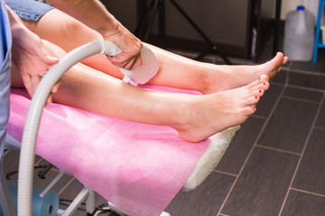 Hair removal cosmetology procedure from a therapist at cosmetic beauty spa clinic. Laser epilation and cosmetology.