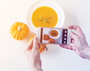 Female hands making mobile photography of pumpkin soup
