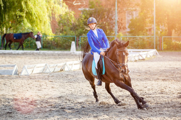 Young girl on bay horse galloping on her course on show jumping competition