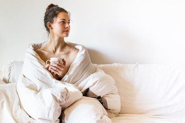 Beautiful young woman covered by blanket is sitting on bed with hot tea