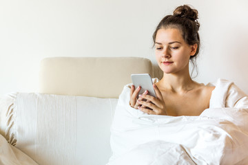 Beautiful young woman covered by blanket is sitting on bed with smart phone