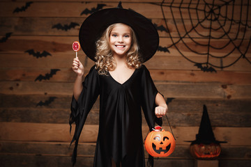 Halloween Witch concept - little witch child with halloween sweet and candy with cheerful smiling. over bat and spider web background.