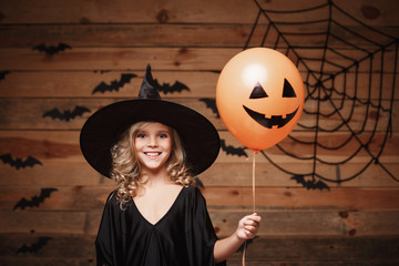 Halloween Witch concept - little caucasian witch child enjoy with halloween balloon. over bat and spider web background.