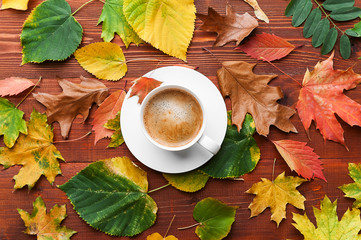 autumn background with a cup of hot aromatic coffee on a wooden table surrounded by autumn leaves and a rug