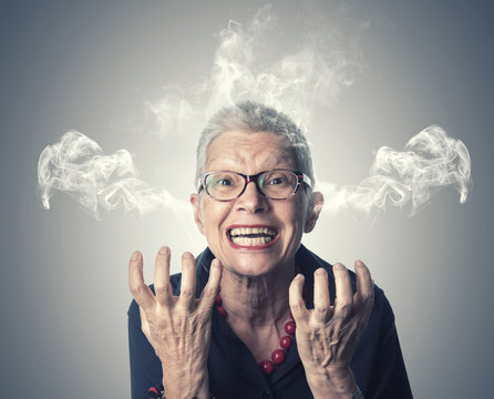 Furious and enraged senior elderly lady with smoke coming out of her ears