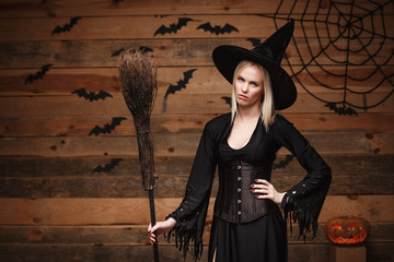Halloween witch concept - Happy Halloween Sexy Witch holding posing with boring facial expression over old wooden studio background.