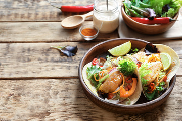 Plate with delicious fish tacos on wooden table