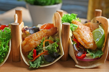 Wooden holder with delicious fish tacos on table, closeup