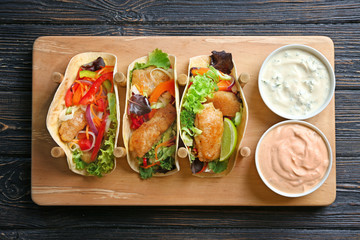 Wooden holder with delicious fish tacos and sauces on table