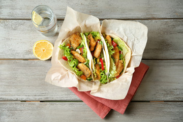 Delicious fish tacos on wooden table