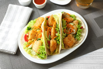 Plate with delicious fish tacos on table