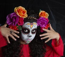 Sugar Skull little girl Halloween costume and makeup. Portrait of a little girl with Halloween costume and makeup of Sugar Skull with white painted face, roses