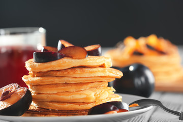 Plate with tasty pancakes and slices of plum on table