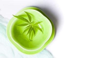 Marijuana leafs in green bowl top view