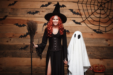 Halloween Concept - Witch mother and little white ghost doing trick or treat celebrating Halloween posing with curved pumpkins over bats and spider web on Wooden studio background.