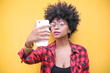Portrait of a cool girl making a selfie in front of a yellow wall