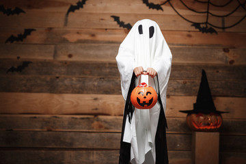 Halloween Concept - little white ghost with halloween pumpkin candy jar doing trick or treat with curved pumpkins over bats and spider web on Wooden studio background.