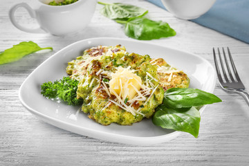 Plate with delicious broccoli pancakes on table
