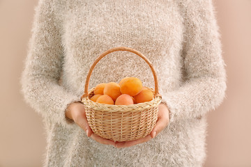 Wall Mural - Woman holding wicker basket with ripe apricots on trendy color background