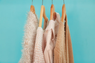 Wall Mural - Apricot and beige clothes on hangers against trendy color background