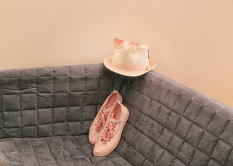 Wall Mural - Apricot sneakers and hat on couch against trendy color background