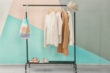 Apricot clothes and accessories on rack near trendy color wall