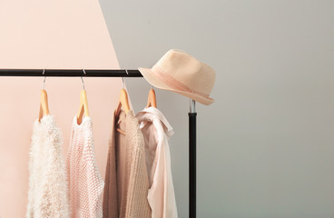 Apricot and beige clothes on hangers against trendy color background Wall mural