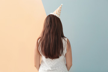 Wall Mural - Woman in apricot party hat against trendy color background