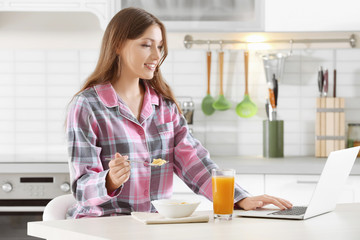 Morning of young beautiful woman having breakfast in kitchen