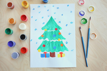 Child's painting of Christmas tree with gifts on table