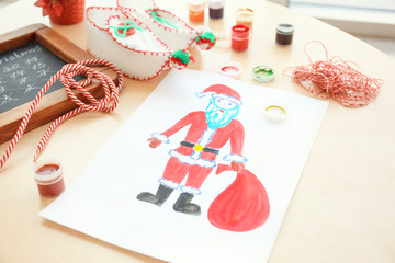 Child's painting of Santa Claus with bag on table