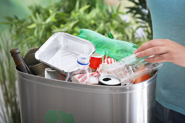 Young woman throwing plastic bottle into litter bin, close up
