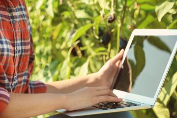 Female farmer holding laptop in field