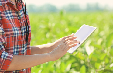 Female farmer holding tablet computer in field