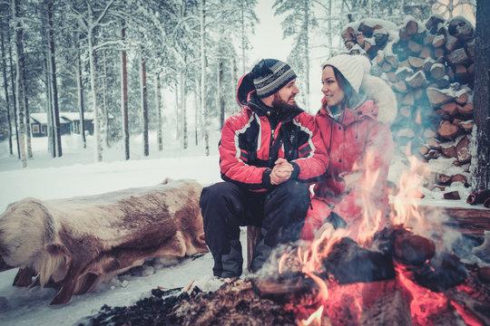Couple near bonefire in winter landscape