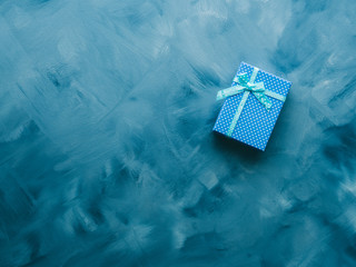 Gift box flat lay on blue background. Holiday surprise concept