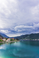 Fototapeten Skandinavien Travel picture natural landscape with blue sea of the boka bay and coast line with colors houses with red roofs, beautiful clouds and lobely boat. Vertical.