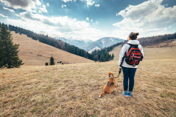 Woman walks with her beagle dog on autumn mountain hill
