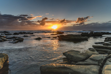 Cloudy and Rocky Sunrise Seascape