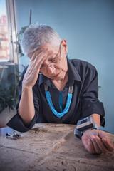 Worried senior lady having a headache and a bad blood pressure