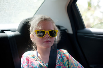 Girl in sunglasses sitting in the back of a car