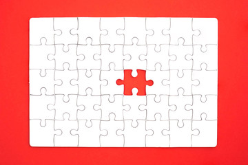 White jigsaw puzzle on red background