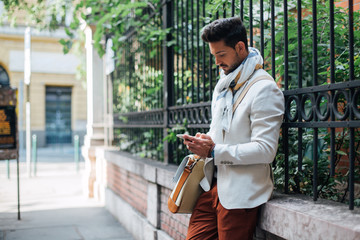 Stylish Man Texting on His Mobile Phone Outdoors