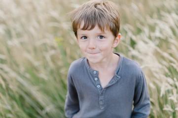Cute child in corn field looks at camera