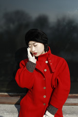 young chinese woman in red coat in front of window