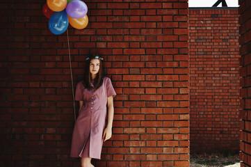 Blonde girl posing against brick walls