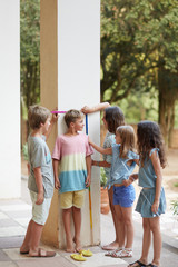 Kids measuring their height in a party