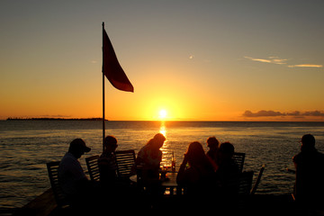 Friends at table watching sunset over the ocean
