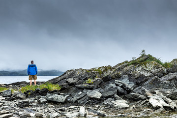 Man standing on the rocky  shore of a lonely lake