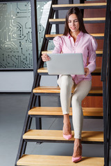 Girl sitting on the stairs working behind the laptop